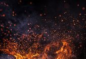 Burning sparks flying. Beautiful flames. Fiery orange glowing flying away particles on black backgro poster