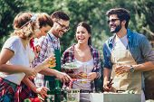 Young Friends Having Fun Grilling Meat Enjoying Barbecue Party. poster