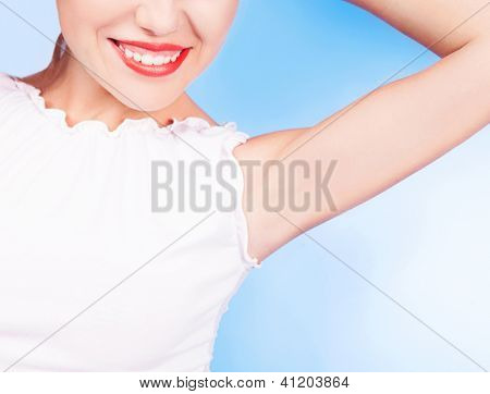 beautiful young woman showing underarms, on blue studio background