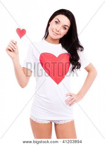smiling young  woman wearing a shirt with a big red heart and holding a Valentine card, isolated against white background