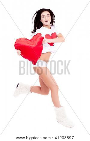 happy jumping young  woman wearing a shirt with a big red heart and holding a heart-shaped pillow, isolated against white background