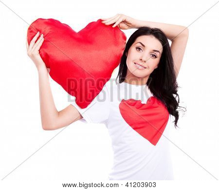 smiling young  woman wearing a  shirt with a big red heart and holding a heart-shaped pillow, isolated against white background