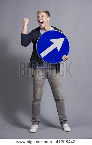 Exited successful man holding round blue sign with arrow pointing upwards with space for text isolated on grey background.