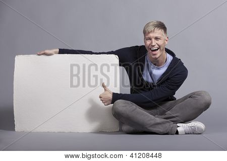 Happy young man giving thumbs up at white blank signboard with space for text while holding it isolated on grey background.