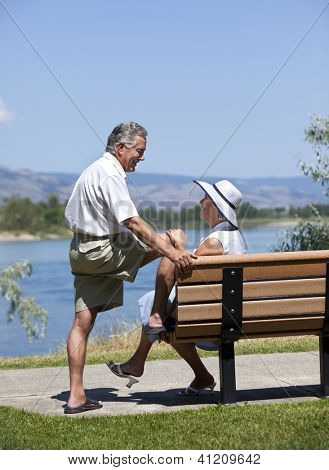 Seniors couple in rural outdoor setting looking at each other, conversing.