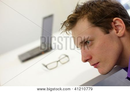 thinking man left profile portrait. eyeglasses and laptop in background