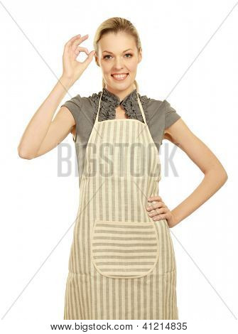 Beautiful happy young  woman wearing kitchen apron and showing ok, isolated on white