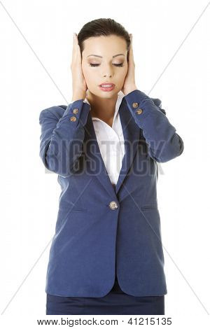 Attractive businesswoman covering her ears with hands, isolated on white