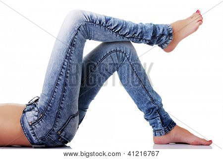 Fit female body in blue jeans, isolated on white