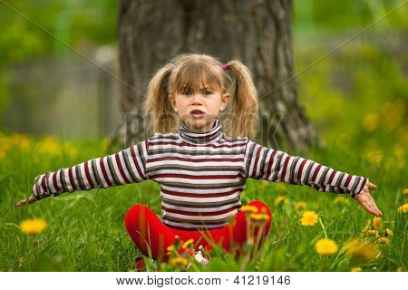Lovely five-year girl sitting in grass and throws up his hands with regret