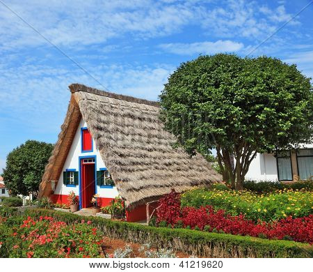 Old house-museum of the first settlers on the island of Madeira. Charming white cottage with a thatched roof and gable small garden with flowers