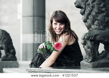 Happy young woman with a flower sitting on the sidewalk