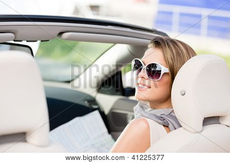 Girl checks the way with the help of the highway map sitting in the car