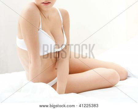 Halfnaked woman sits on the double bed with white bedclothes