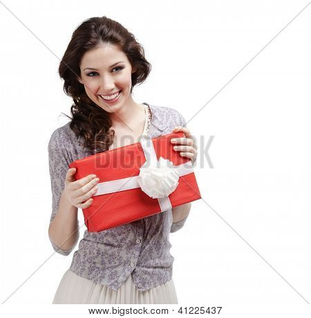 Young woman hands a present wrapped in red paper with white bow, isolated on white