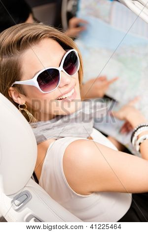 Girl lost the way and checks the way with the help of the highway map sitting in the car
