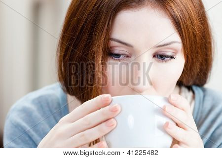 Woman with cup of tea has a rest at the cosy restaurant
