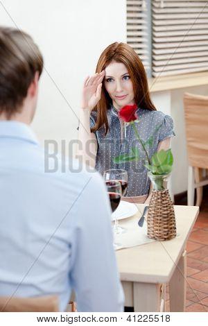 Par é o restaurante sentado à mesa com vaso e vermelho levantou-se nele