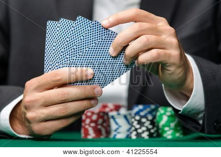 Gambler playing poker cards with chips on the table. Challenge to the casino
