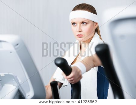 Young woman training on training apparatus in gym
