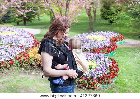 Young Mother Carrying Baby Son In Rucksack In Park