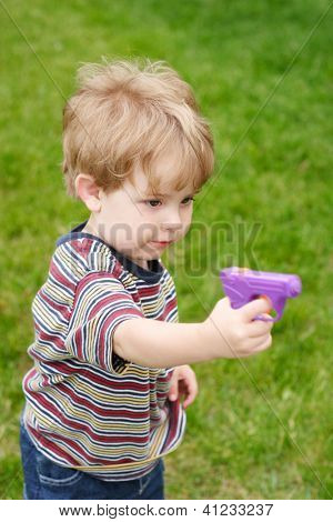 Young boy aiming a  water gun