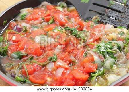 Fried onion and parsley and tomatoes in a pan, part of the preparation for a greek stuffed aubergine dish, Imam Baildi or Imam melitzanes