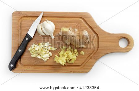 Finely chopped garlic and ginger next to a part used garlic bulb and a ginger rhizome. The two are a basic combination in an enormous number of Asian foods
