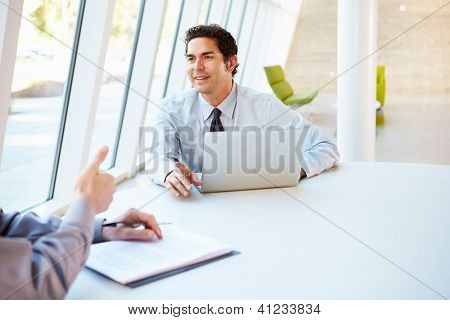 Two Businessmen Having Meeting Around Table In Modern Office