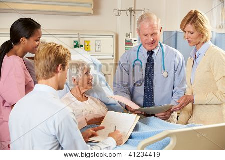 Medical Team Visiting Senior Female Patient In Bed