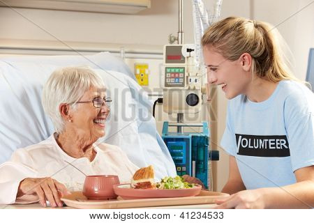 Teenage Volunteer Serving Senior Female Patient Meal In Hospital Bed