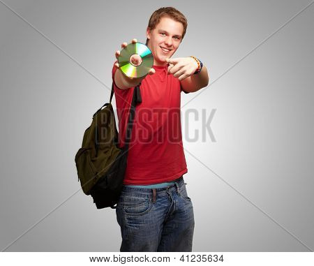 Portrait Of A Man With Compact Disc On Gray Background