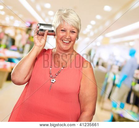 Senior Woman Hearing On Metal Tin Can Phone, Indoors