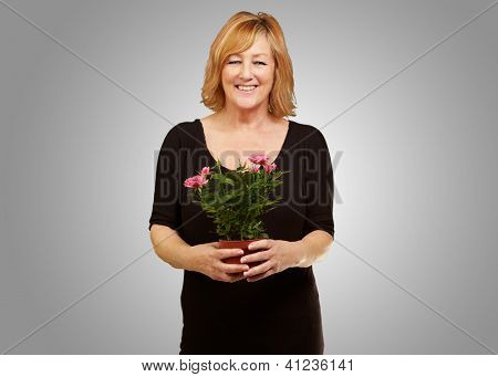 Woman holding flower pot isolated on gray background
