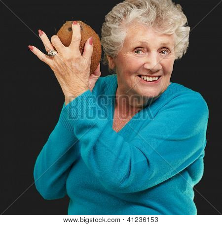 Senior happy woman holding coconut isolated on black background