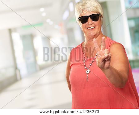 Portrait Of A Senior Woman Showing Victory Sign, Indoor