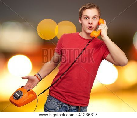 Portrait of a young man talking on vintage phone, outdoor