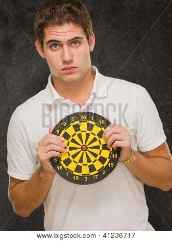 Young Man Holding Dartboard against a grunge background