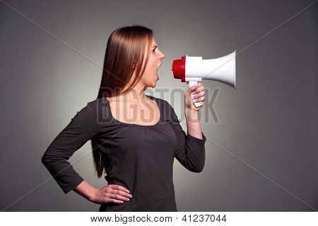 attractive young woman holding megaphone over dark background