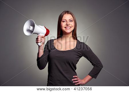 friendly young woman holding megaphone and smiling. studio shot over dark background