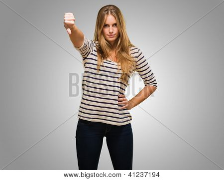 Young Woman Showing Thumb Down Sign against a grey background