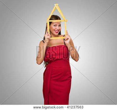 Happy Young Woman Looking Through House Frame against a grey background