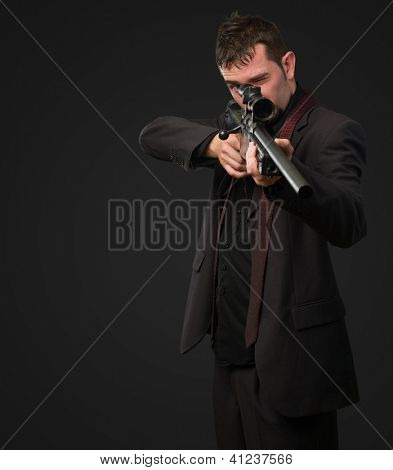 Man in suit pointing with a rifle against a black background