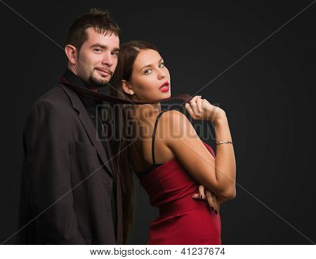Beautiful Woman Holding Businessman Tie against a black background