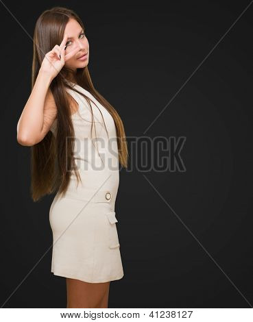 Beautiful Smiling Woman Showing Two Fingers In Front Of Eye against a black background