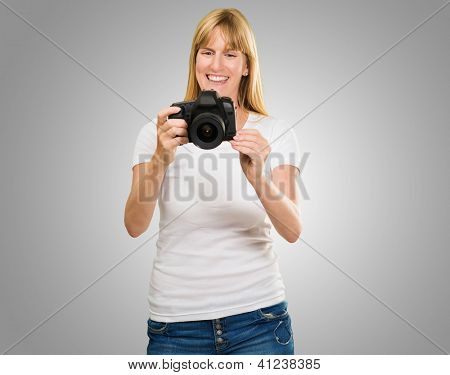 Happy Young Woman Looking At Camera against a grey background