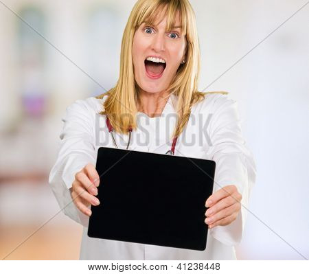 surprised doctor holding a digital tablet against an abstract background