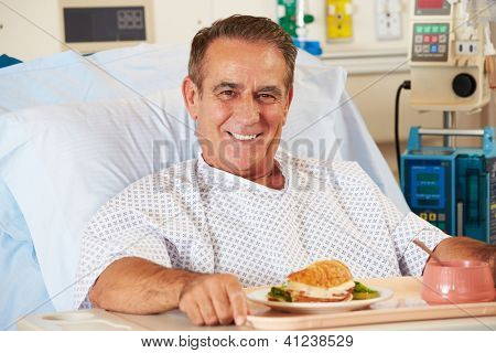 Male Patient Enjoying Meal In Hospital Bed