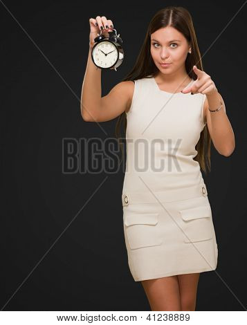 Woman Holding Alarm Clock and pointing against a black background