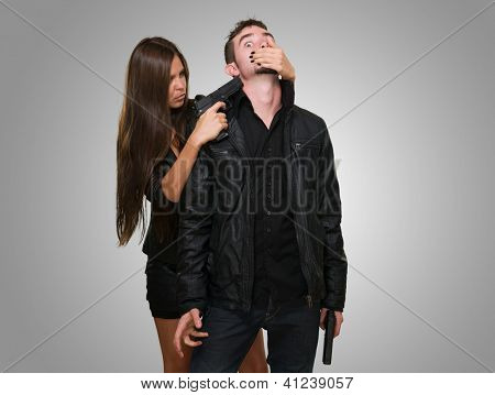 Criminal With A Gun Threatening Young Woman against a grey background